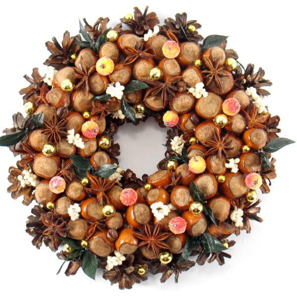 Mały wianek świąteczny z orzechów laskowych, wykonany na podkładzie słomianym z szyszek, orzechów suchych roślin i ozdób. Średnica wianka wynosi 22 cm.