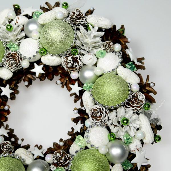 Wianek świąteczny biało-zielony wykonany na podkładzie słomianym z szyszek, bombek, suchych i sztucznych roślin i świątecznych ozdób.
