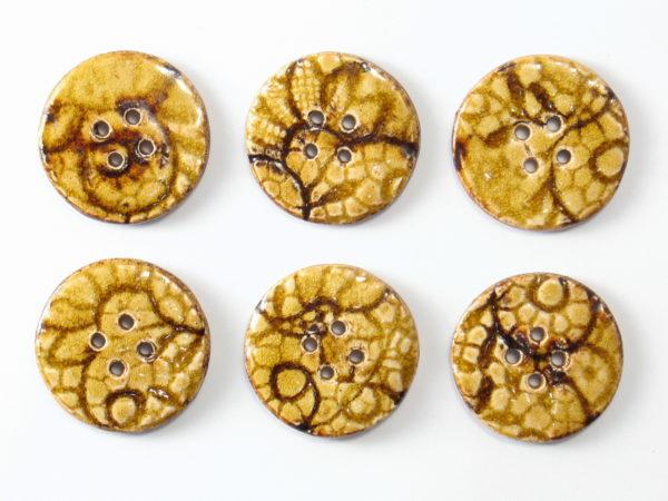 Guzik ceramiczny okrągły brązowo-beżowy, wykonany z jasnej gliny i pokryty jednostronnie błyszczącymi szkliwami. Rękodzieło.