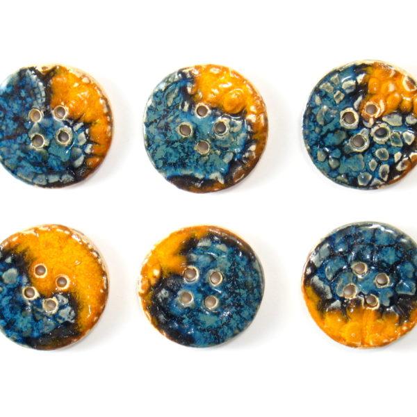Guzik ceramiczny okrągły pomarańczowo-granatowy, wykonany z jasnej gliny i pokryty jednostronnie błyszczącymi szkliwami. Rękodzieło.