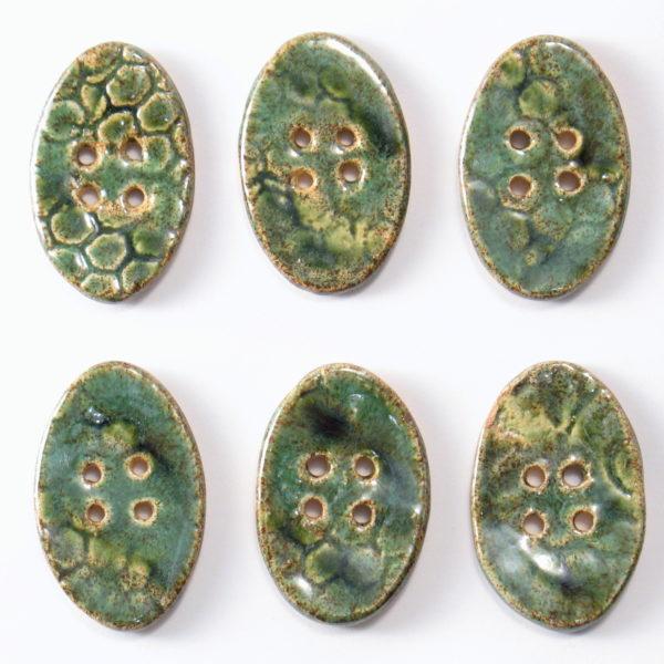 Guzik ceramiczny owalny zielony, wykonany z jasnej gliny i pokryty jednostronnie błyszczącymi szkliwami. Rękodzieło. Wymiary guzika - 4 x 2,5 cm