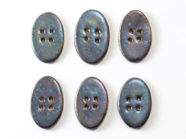 Guzik ceramiczny owalny grafitowy, wykonany z jasnej gliny i pokryty jednostronnie błyszczącymi szkliwami. Rękodzieło. Wymiary guzika - 4 x 2,5 cm