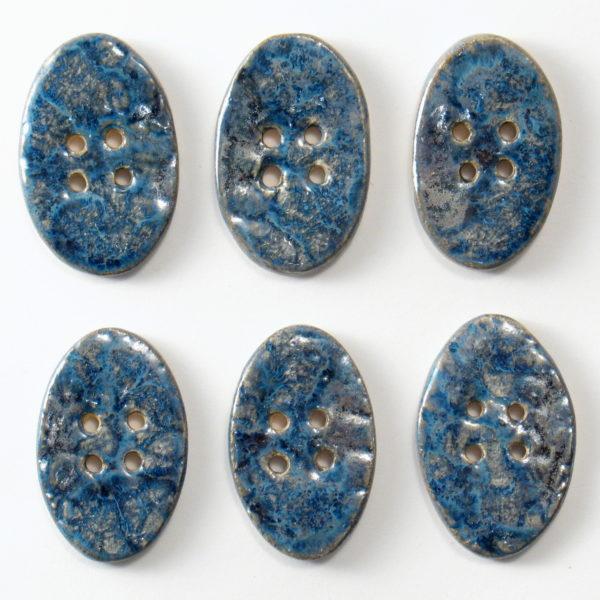 Guzik ceramiczny owalny niebiesko-granatowy, wykonany z jasnej gliny i pokryty jednostronnie błyszczącymi szkliwami. Rękodzieło. Wymiary guzika - 4 x 2,5 cm