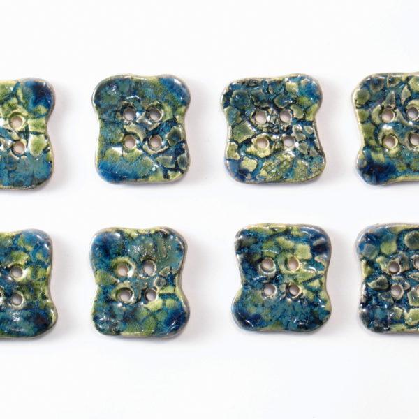 Guzik ceramiczny nieregularny granatowo-zielony, wykonany z jasnej gliny i pokryty jednostronnie błyszczącymi szkliwami. Rękodzieło. Wymiary - 2,5 x 2,8