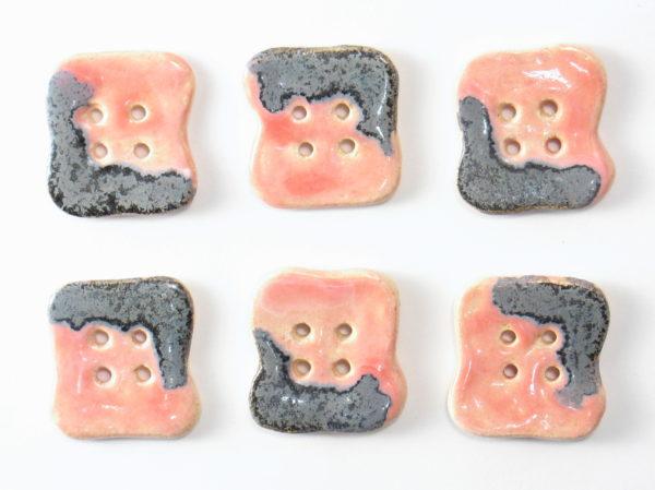 Guzik ceramiczny nieregularny szaro-różowy, wykonany z jasnej gliny i pokryty jednostronnie błyszczącymi szkliwami. Rękodzieło. Wymiary - 2,5 x 2,8