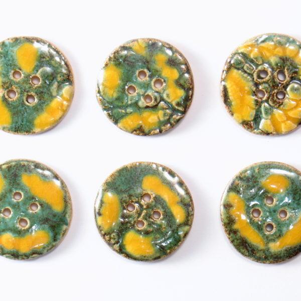 Guzik ceramiczny okrągły żółto-zielony, wykonany z jasnej gliny i pokryty jednostronnie błyszczącymi szkliwami. Rękodzieło.