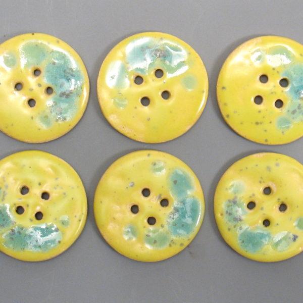Guzik ceramiczny okrągły żółto-turkusowy, wykonany z jasnej gliny i pokryty jednostronnie błyszczącymi szkliwami. Rękodzieło.