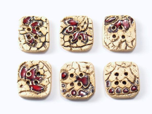Guzik ceramiczny nieregularny z koronką, wykonany z jasnej gliny i pokryty jednostronnie błyszczącymi szkliwami. Rękodzieło. Wymiary - 2,5 x 2,8