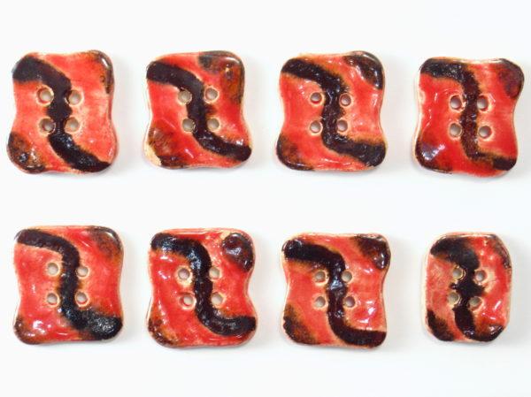 Guzik ceramiczny nieregularny czerwono-brązowy, wykonany z jasnej gliny i pokryty jednostronnie błyszczącymi szkliwami. Rękodzieło. Wymiary - 2,5 x 2,8