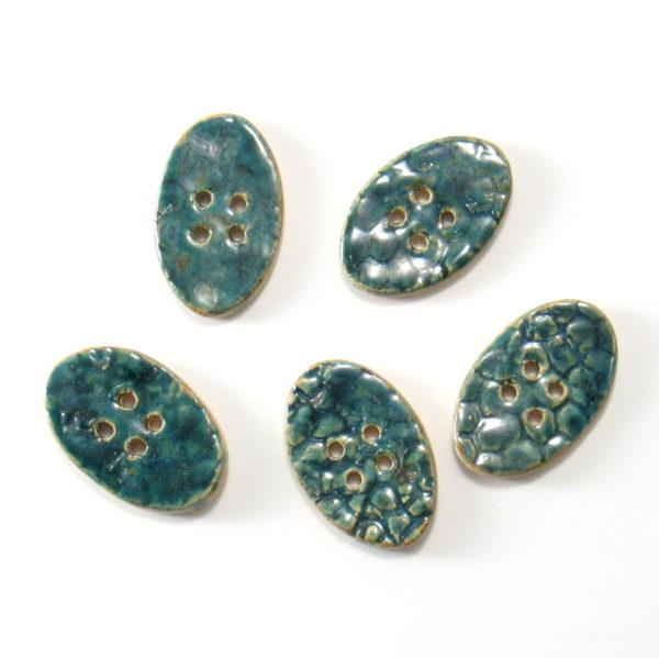 Guzik ceramiczny owalny turkusowy, wykonany z jasnej gliny i pokryty jednostronnie błyszczącymi szkliwami. Rękodzieło. Wymiary guzika - 4 x 2,5 cm