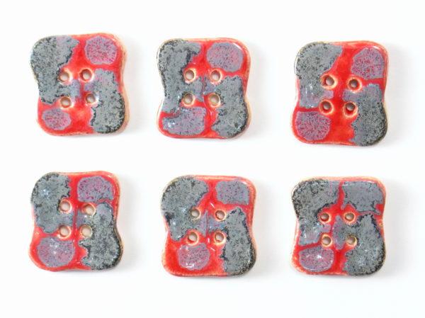 Guzik ceramiczny nieregularny szaro-czerwony, wykonany z jasnej gliny i pokryty jednostronnie błyszczącymi szkliwami. Rękodzieło. Wymiary - 4 x 2,5 cm