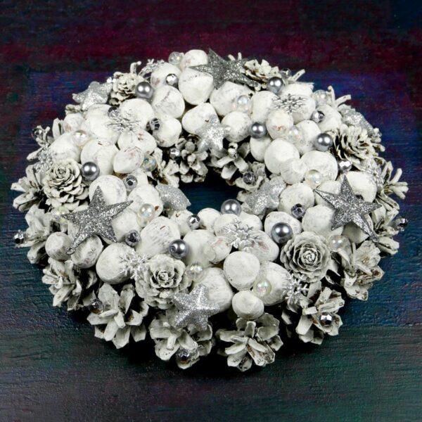 Biały wianek świąteczny z orzechami wykonany na podkładzie słomianym z szyszek, suchych roślin i świątecznych ozdób. Średnica 23 cm.