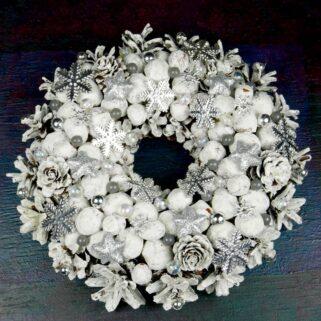 Mały biały wianek z orzechami wykonany na podkładzie słomianym z szyszek, suchych roślin i świątecznych ozdób. Średnica wianka wynosi 23 cm.