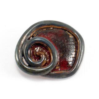 Broszka ceramiczna Zawijasek wspaniale zaprezentuje się szczególnie w połączeniu z ubraniami z wełny